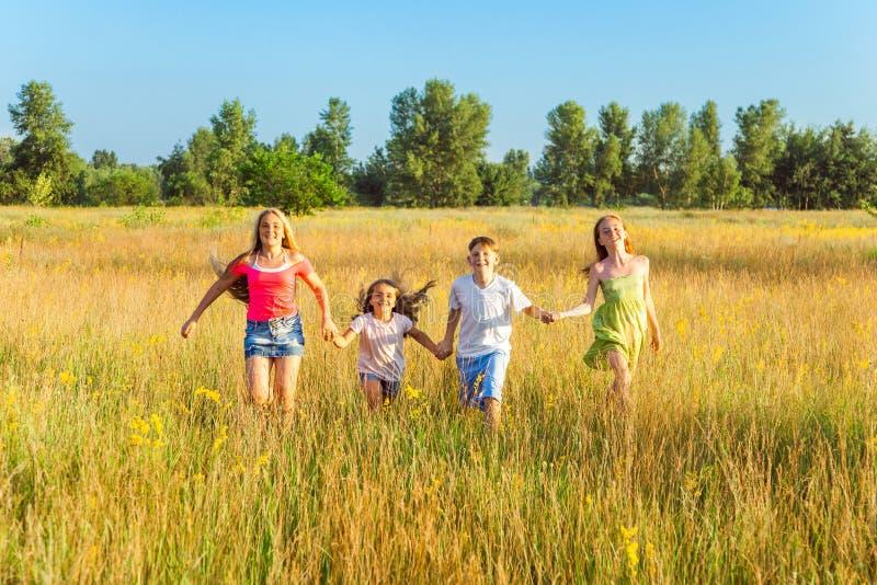 Vier glückliche schöne Kinder, die am schönen Sommertag zusammenrücken spielend laufen stockbild