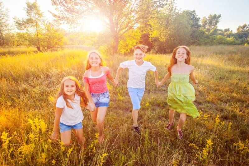 Vier glückliche schöne Kinder, die am schönen Sommertag zusammenrücken spielend laufen stockfotografie