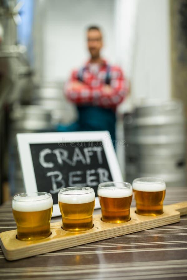 Vier glazen ambachtbier op het dienblad van de biermonstertrekker stock foto