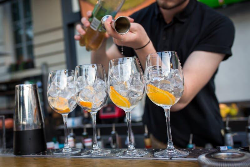 Vier glazen die zich op de bar bevinden De glazen zijn met ijs en sinaasappel De barman giet alcohol in glazen van het meten royalty-vrije stock afbeeldingen