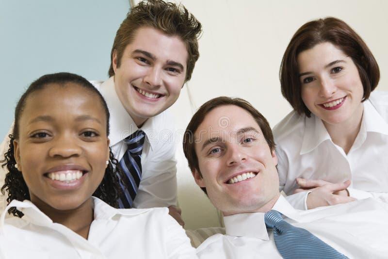 Vier glimlachende jonge bedrijfsmensen. royalty-vrije stock afbeelding