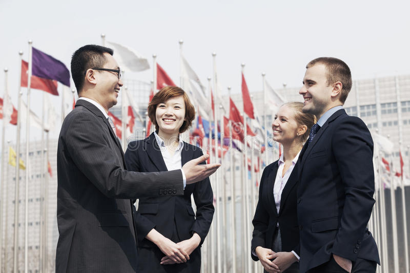 Vier glimlachende multi-etnische bedrijfsmensen die in openlucht in Peking, China spreken royalty-vrije stock afbeeldingen