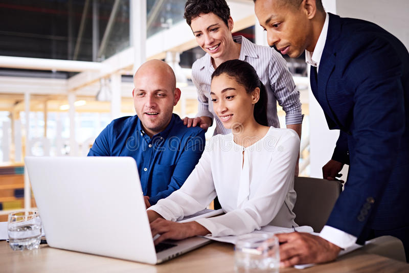 Vier goed geklede diverse ondernemers die het laptop scherm bekijken royalty-vrije stock afbeelding