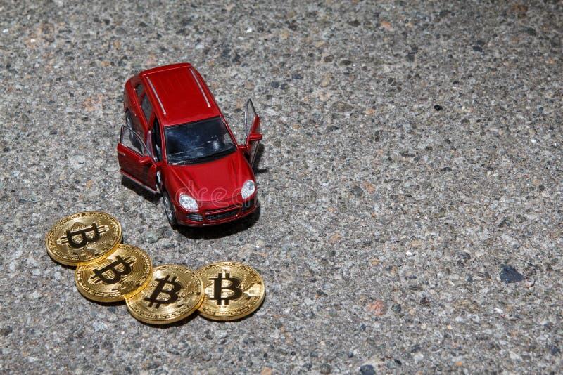 Vier goldene Bitcoin-Münzen nahe roter Luxuscrossover-fahrzeug-Nahaufnahme auf Asphalt masern Hintergrund mit einem copyspace stockbild