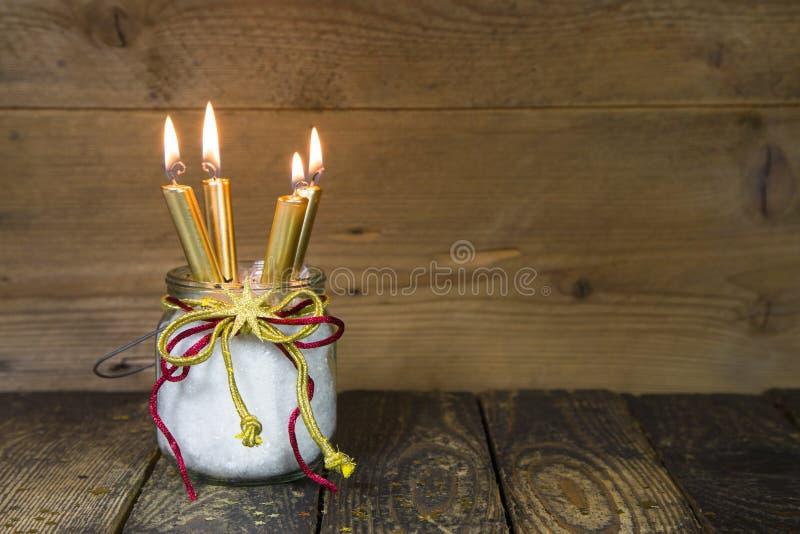Vier goldene Kerzen, traditionelle Weihnachtsdekoration auf einem Anflehung lizenzfreie stockfotos