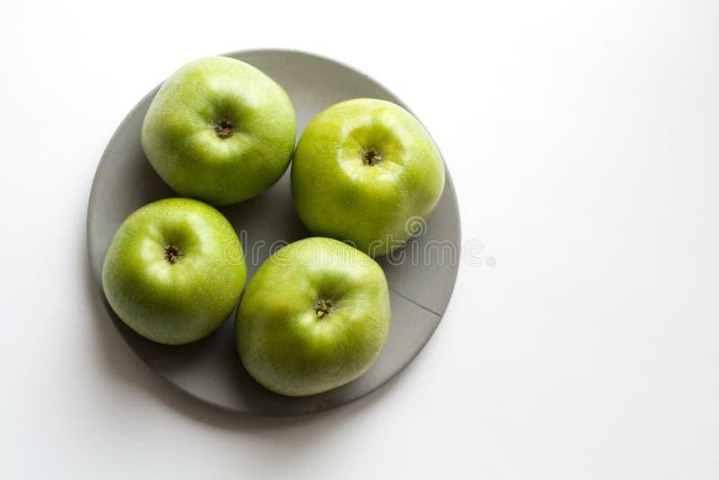 Vier groene appelen op grijze plaat van hierboven stock afbeeldingen