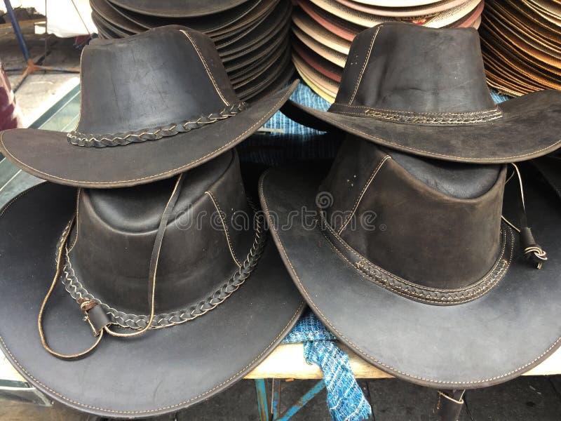 Vier grote zwarte hoeden van de leercowboy die bovenop elkaar worden opgestapeld royalty-vrije stock afbeeldingen