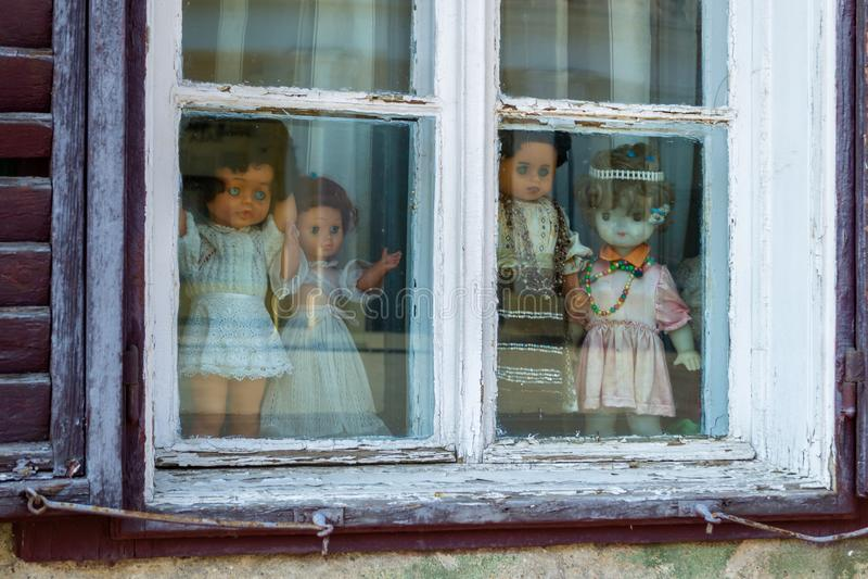 Vier gruselige Puppen gekleidet in der weißen und mit traditionellen rumänischen Kleidung, angezeigt in einem Fenster, beim Betra stockbild
