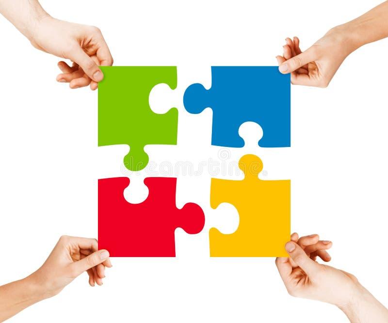 Vier Hände, die Puzzlespielstücke anschließen lizenzfreie stockfotos