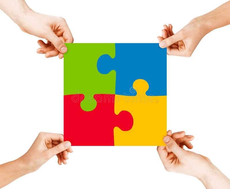 Vier Hände, die Puzzlespielstücke anschließen stockbild