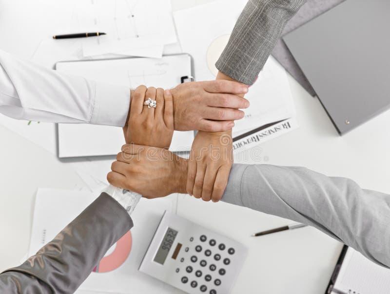 Vier Hände zusammen in der Einheit am Businessmeeting lizenzfreie stockfotografie