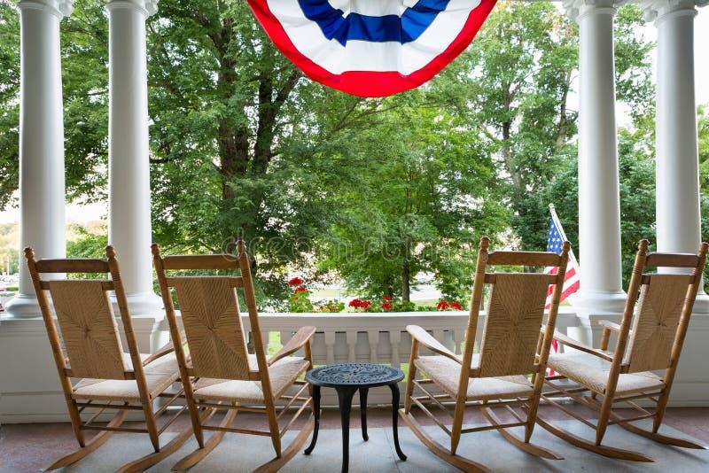 Vier hölzerne Schaukelstühle und die amerikanische Flagge stockbild