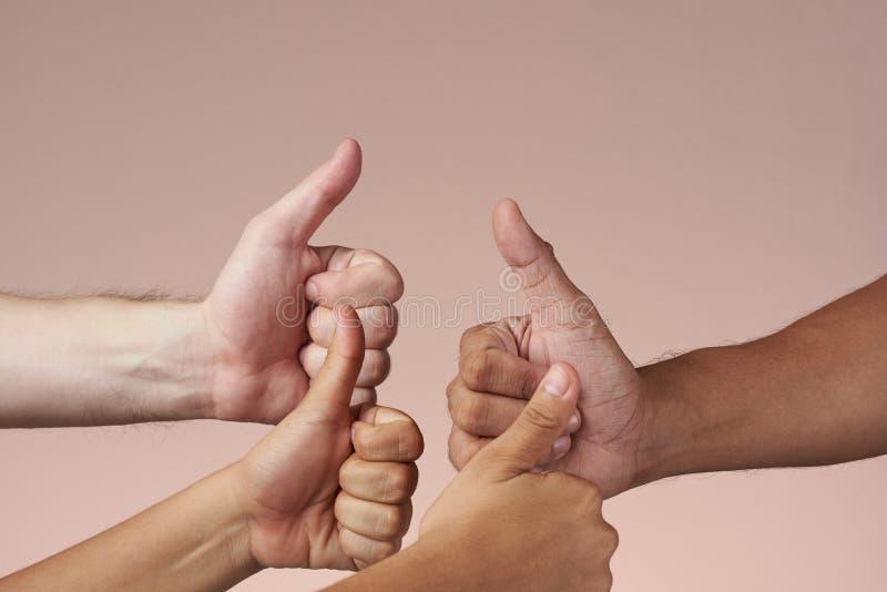 Vier handen met duim-omhoog stock afbeelding