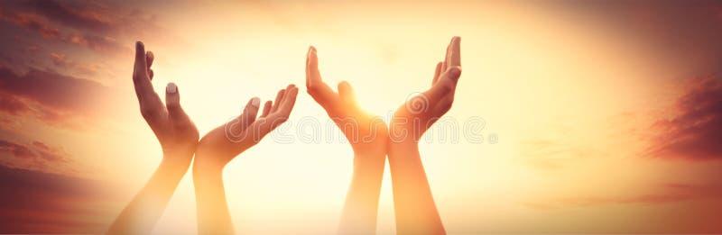 Vier handen op zonsondergang royalty-vrije stock afbeelding