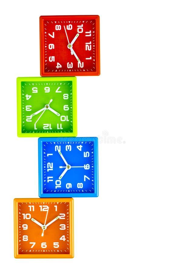 Vier heldere vierkante wekkerstribune op elkaar Rode, groene, blauwe, oranje wekkers royalty-vrije stock foto's