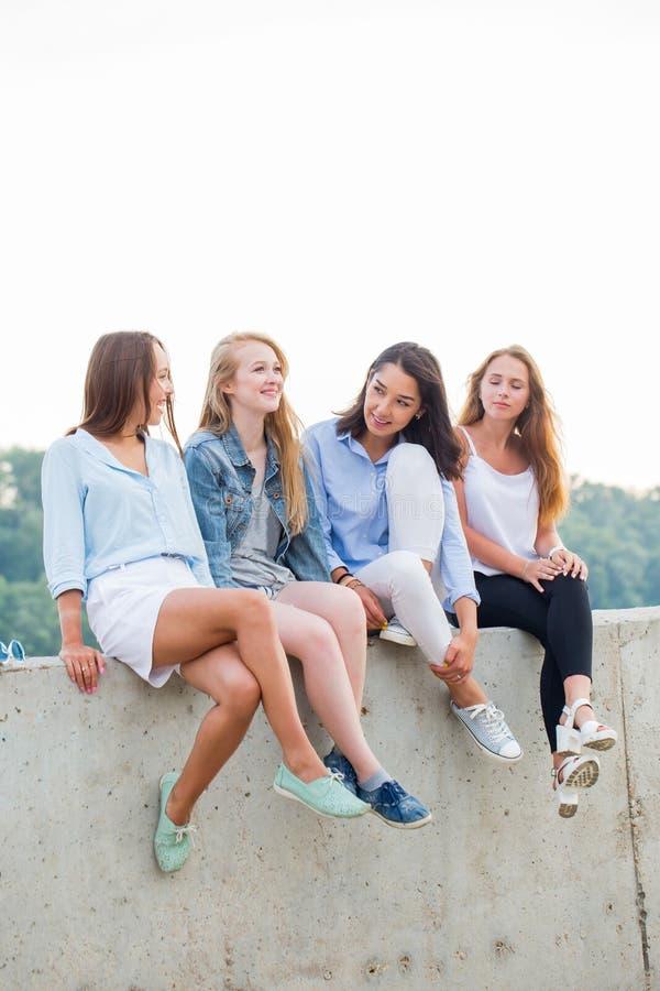 Vier het aantrekkelijke jonge studentes zitten die na school of Universiteit rusten stock foto