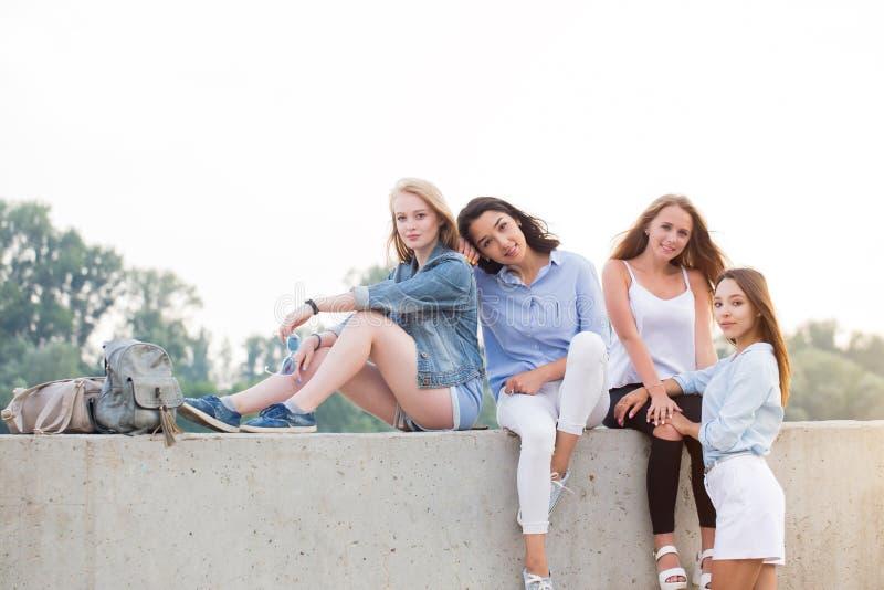 Vier het aantrekkelijke vrouwelijke studenten openlucht stellen terwijl het zitten in het Park, die camera bekijken stock afbeeldingen