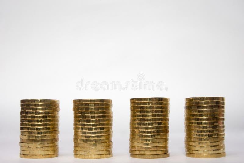 Vier identische Höhe des Stapels Münzen auf einem hellen Hintergrund, der Spitzenplatz für eine Aufschrift stockfotos
