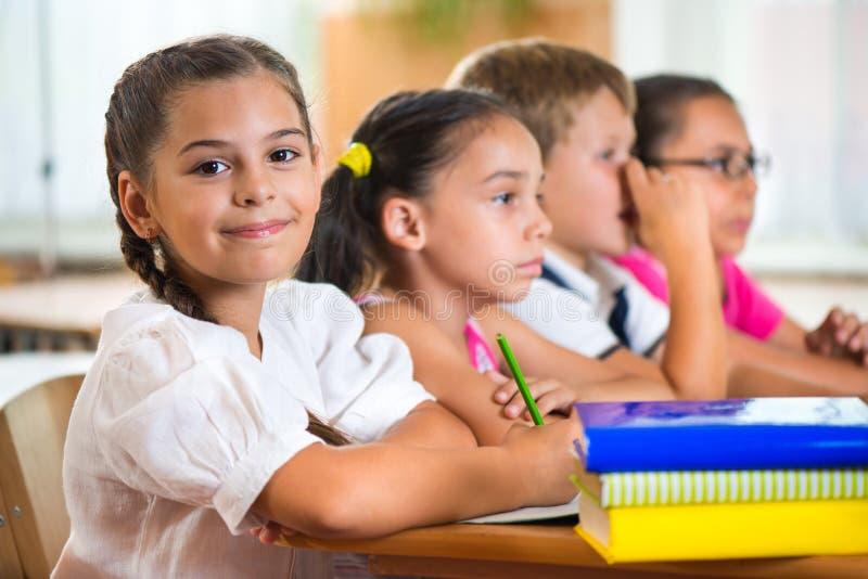 Vier ijverige leerlingen die bij klaslokaal bestuderen stock foto's