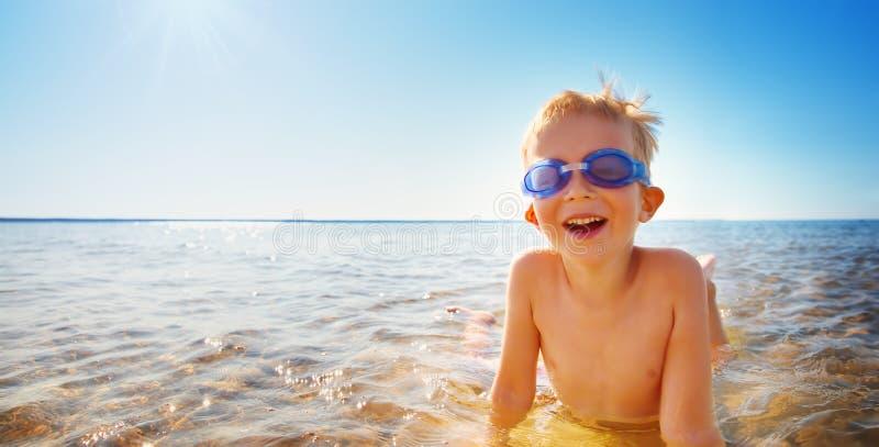 Vier Jahre alte Junge, die am Strand mit schwimmenden Gläsern spielen stockfotografie