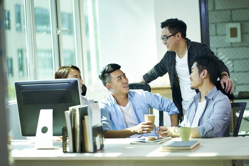 Vier jonge Aziatische bedrijfsmensen die in bureau babbelen stock afbeeldingen
