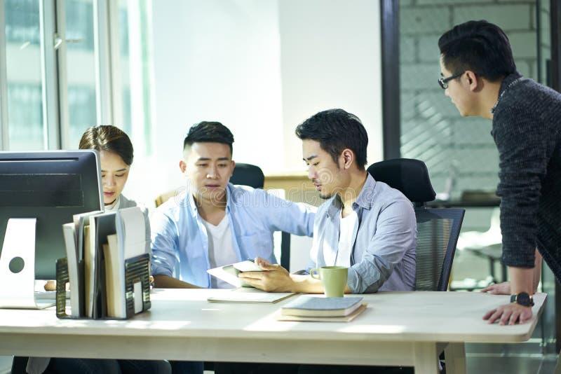 Vier jonge Aziatische ondernemers die zaken in bureau bespreken royalty-vrije stock foto