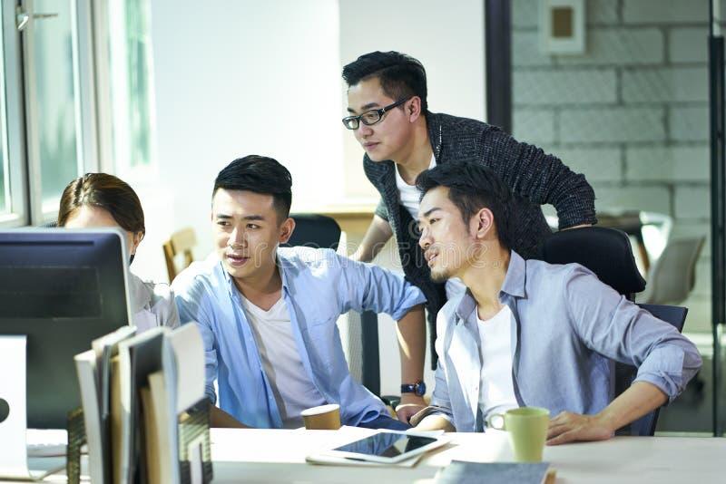Vier jonge Aziatische ondernemers die zaken in bureau bespreken stock afbeelding