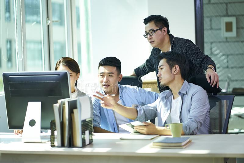 Vier jonge Aziatische ondernemers die zaken in bureau bespreken stock foto's