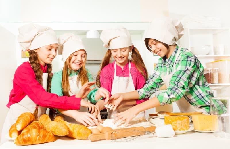 Vier jonge bakkers die deeg kneden bij de keuken royalty-vrije stock foto