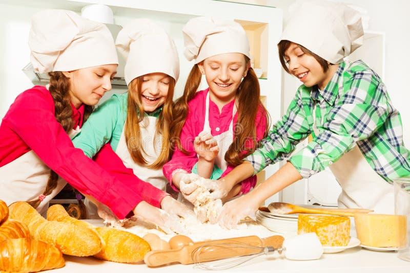 Vier jonge bakkers die deeg kneden bij de keuken royalty-vrije stock afbeelding