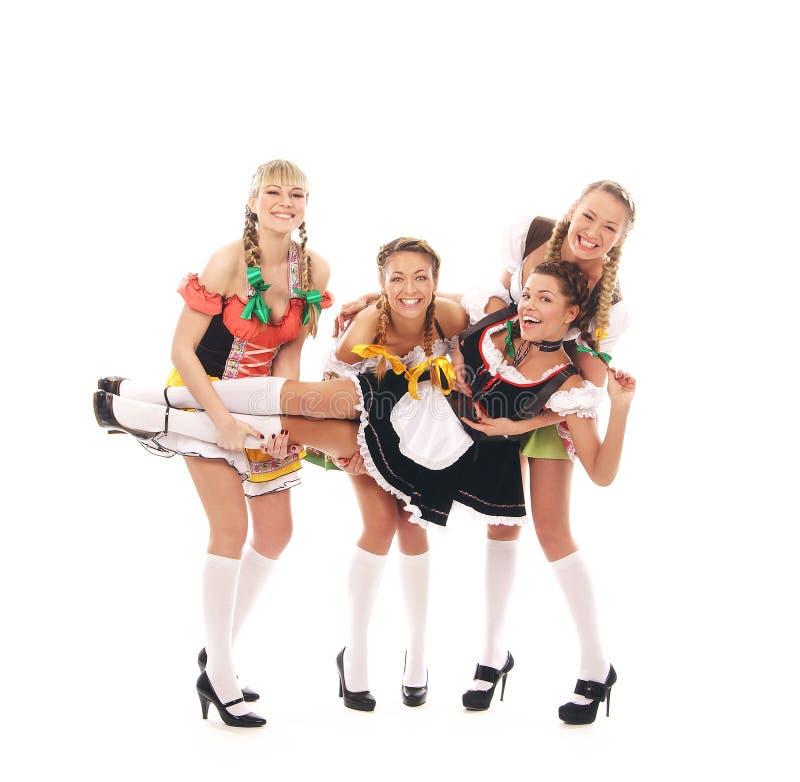 Vier jonge en gelukkige vrouwen in Beierse kleren royalty-vrije stock afbeeldingen