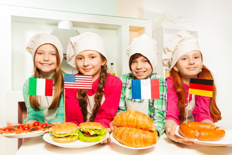 Vier jonge geitjes die maaltijd van verschillende landen vertegenwoordigen stock foto