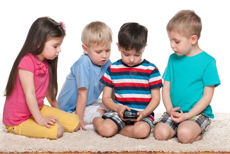 Vier jonge geitjes met een gadget op het tapijt royalty-vrije stock foto's