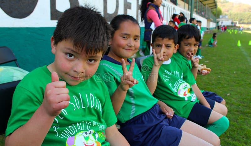 Vier jonge geitjesbegroetingen aan de camera in een sportevenement in Mexico royalty-vrije stock afbeelding