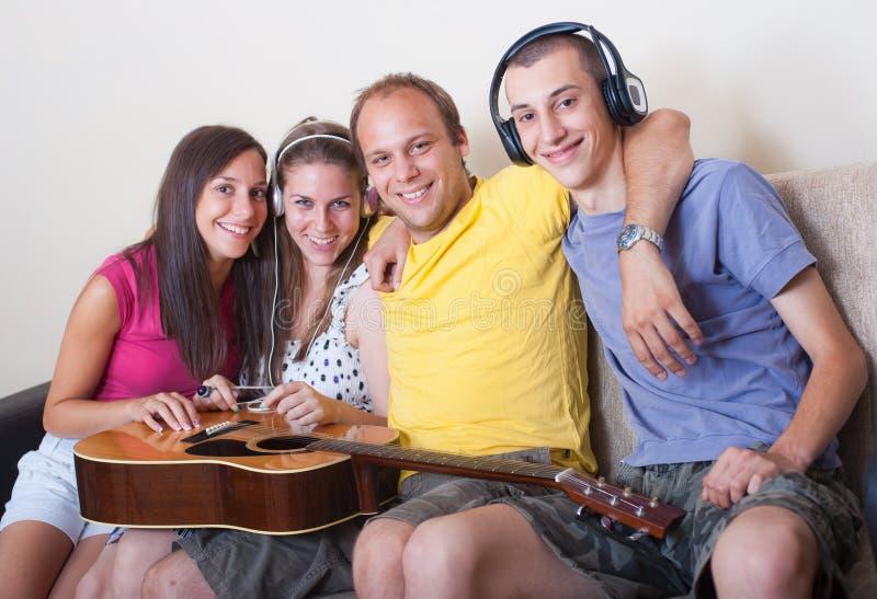 Vier Jonge Mensen Met Gitaar En Hoofdtelefoons Royalty-vrije Stock Fotografie