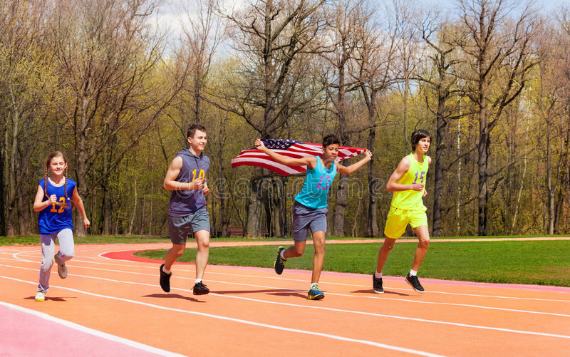 Vier jonge sprinters die Amerikaanse vlag op spoor golven stock foto