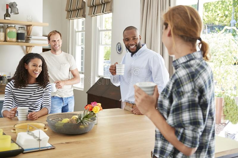 Vier jonge volwassen vrienden die koffie in de keuken hebben stock foto's