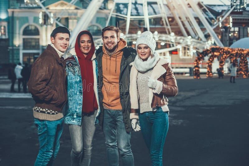 Vier jonge vrienden die terwijl zich het verenigen in openlucht glimlachen royalty-vrije stock afbeelding