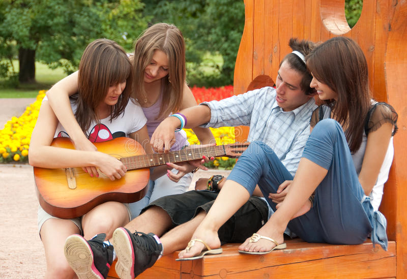 Vier jonge vrienden spelen de gitaar