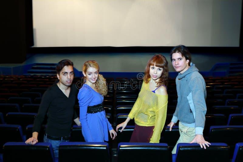 Vier jonge vriendentribune in de zaal van het bioskooptheater stock afbeeldingen