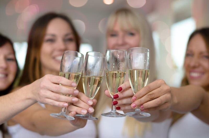 Vier jonge vrouwen die met champagne roosteren stock foto