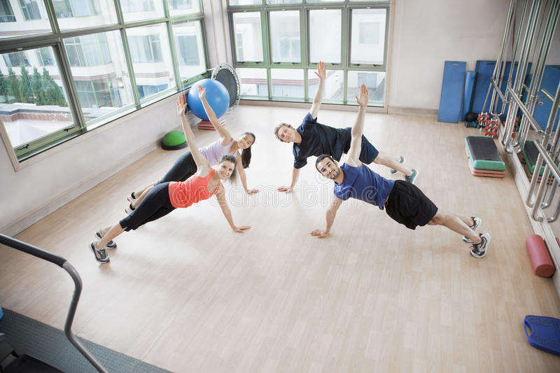 Vier jongeren die en zich de camera in een aerobicsklasse uitrekken bekijken stock afbeeldingen