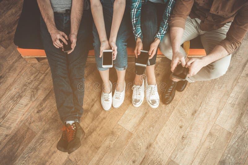 Vier jongeren verkiest online mededeling over telefoons stock afbeeldingen