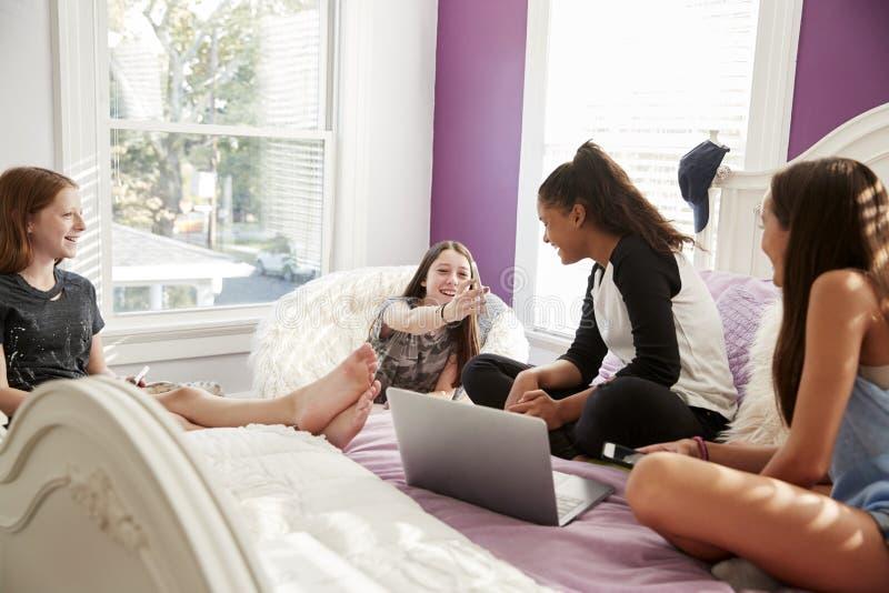 Vier jugendlich Mädchen, die Telefone und Laptop im Schlafzimmer betrachten stockfotografie