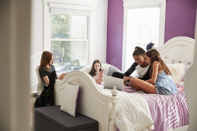 Vier jugendlich Mädchen hängen heraus unter Verwendung des Laptops und der Telefone im Schlafzimmer stockfotografie