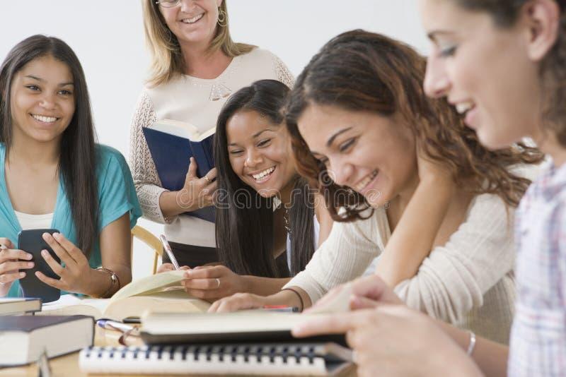 Vier jugendlich Mädchen und Lehrer. lizenzfreie stockbilder