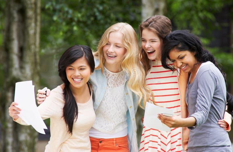Vier Jugendlichen, die erfolgreiche Prüfungs-Ergebnisse feiern stockfoto
