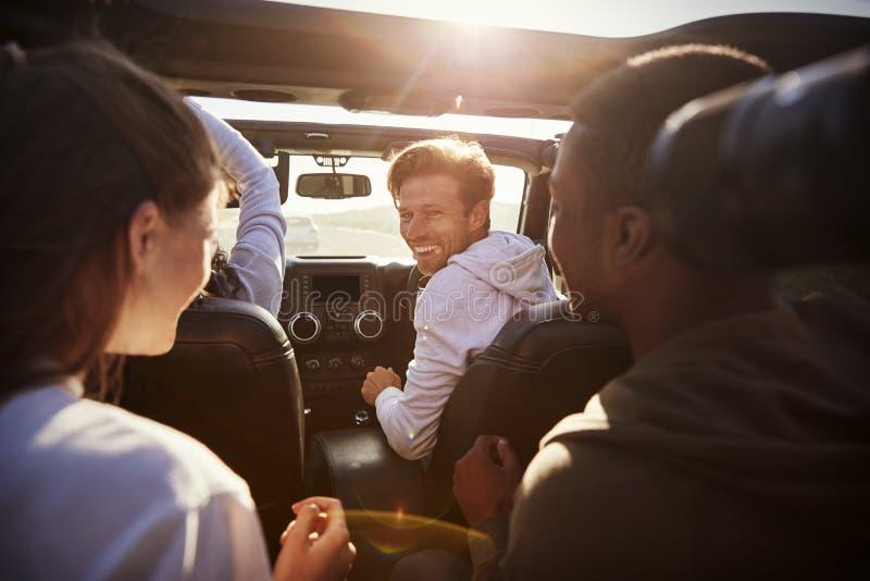 Vier junge erwachsene Freunde zusammen in einem Auto auf einer Autoreise lizenzfreie stockfotografie