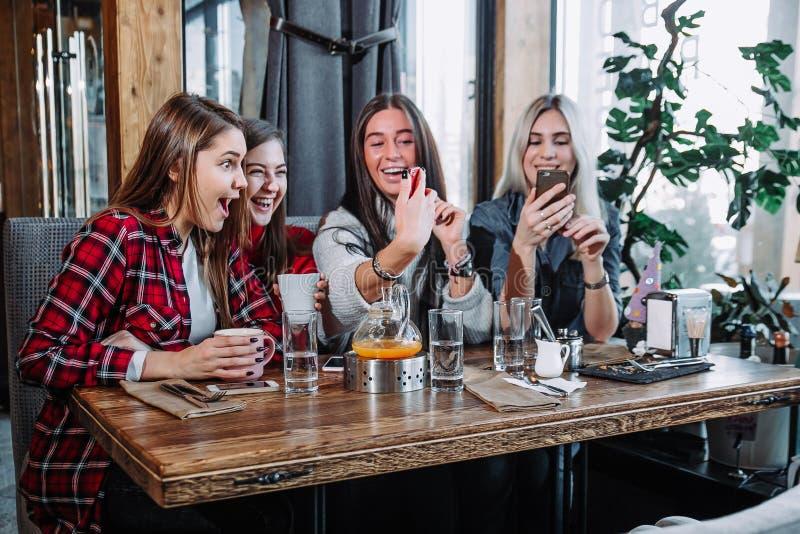 Vier junge Frauen, die im Café unter Verwendung des intelligenten Telefons sitzen und lustiges Gespräch haben stockfotografie