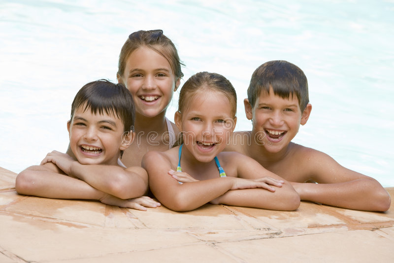 Vier junge Freunde beim Swimmingpoollächeln lizenzfreies stockbild
